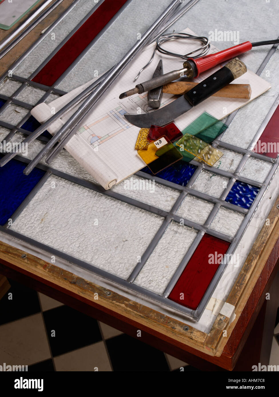 Equipment and materials needed to make leaded glass windows including soldering iron various kinds of glass sketch and lead - Stock Image