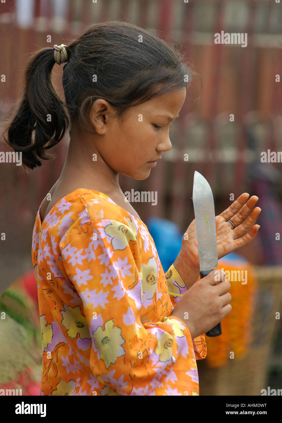 Young flower vendor with knife and henna painted hands at market Kathmandu Nepal - Stock Image