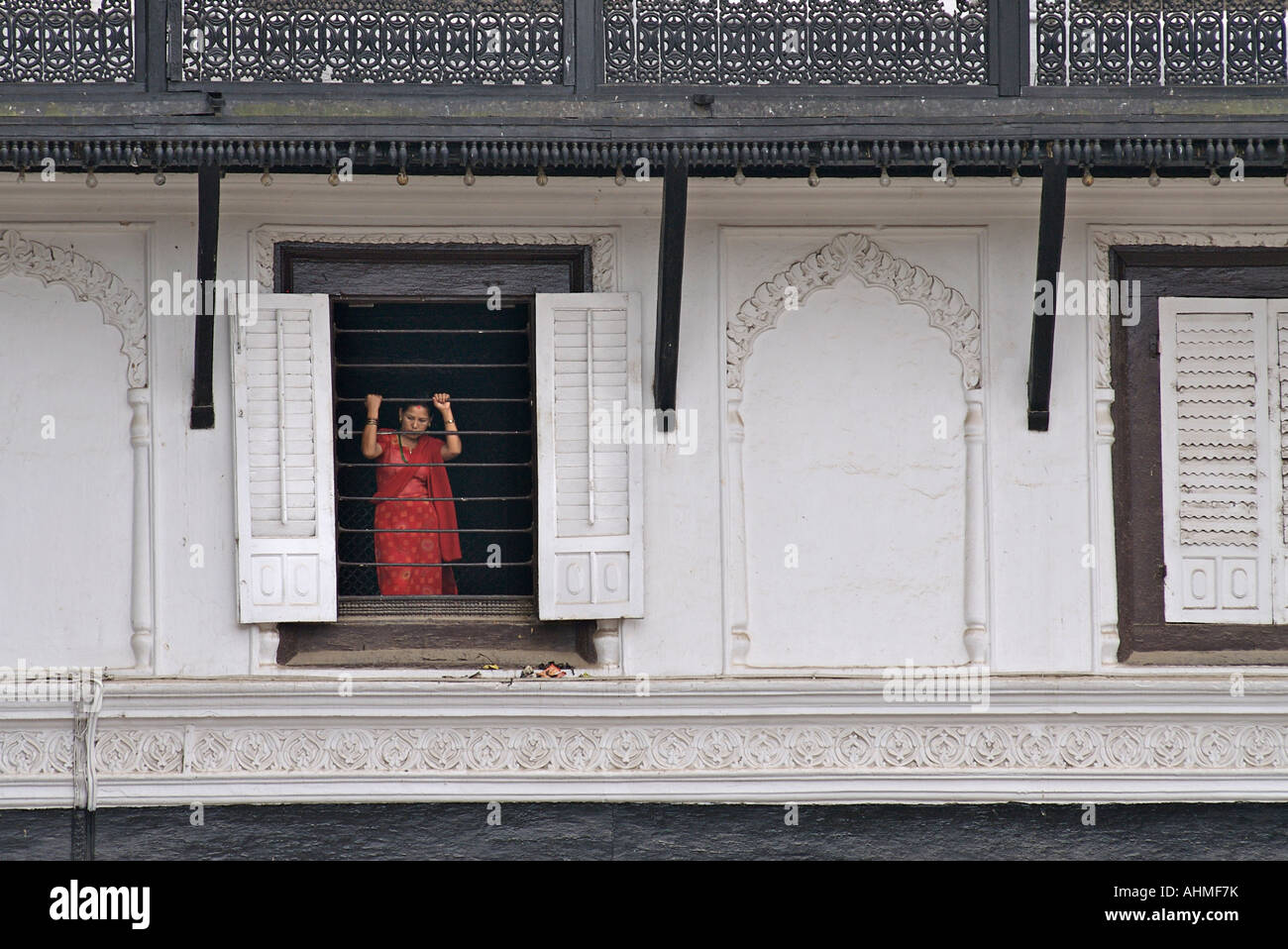 Woman in bright clothes standing in a window above Durbar Square Kathmandu Nepal - Stock Image