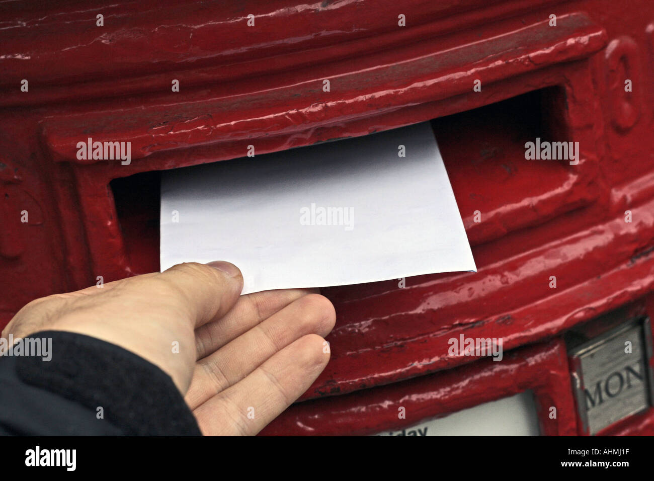 Posting a letter in the postbox - Stock Image