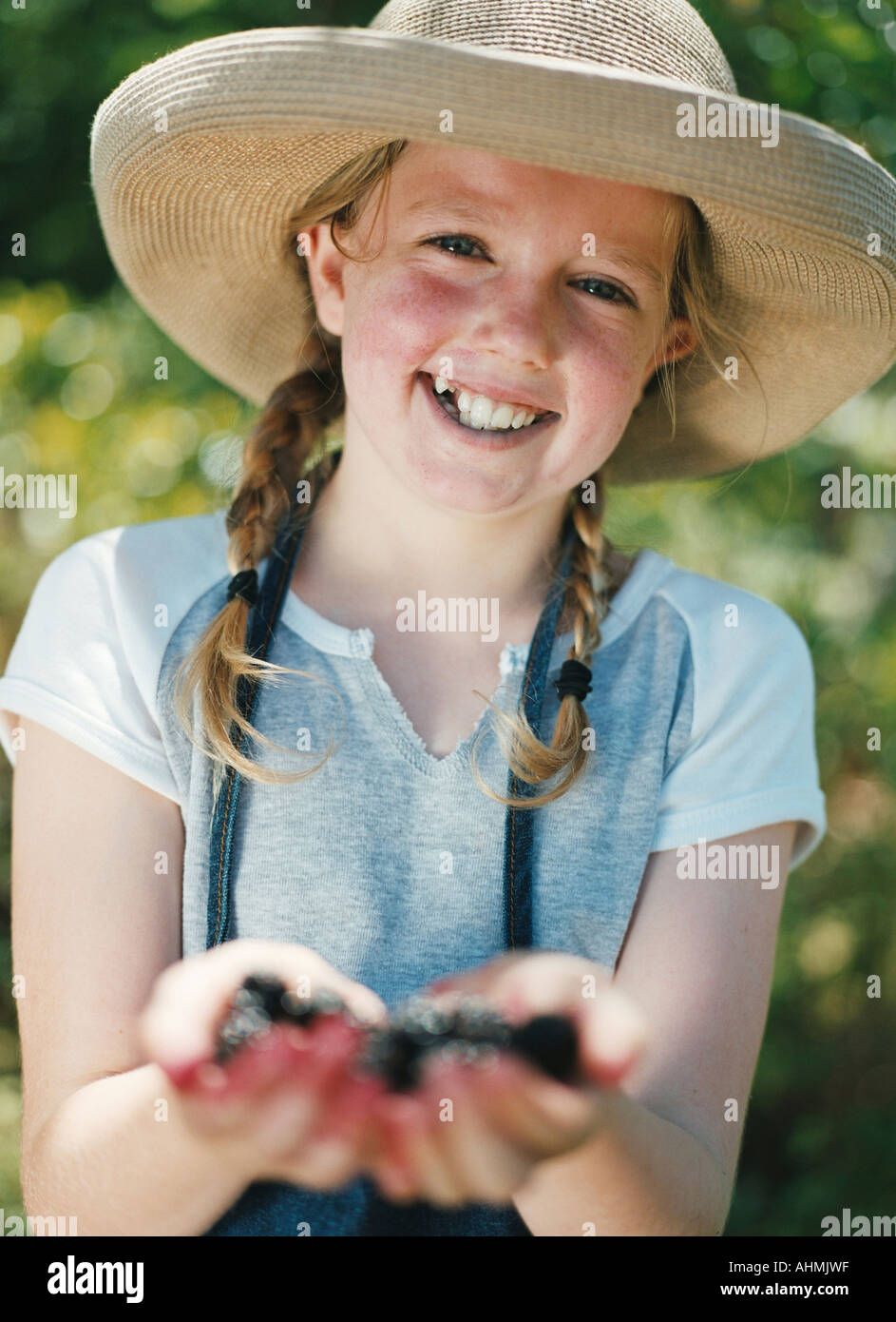 Young girl proudly displays wild blackberries she has picked - Stock Image