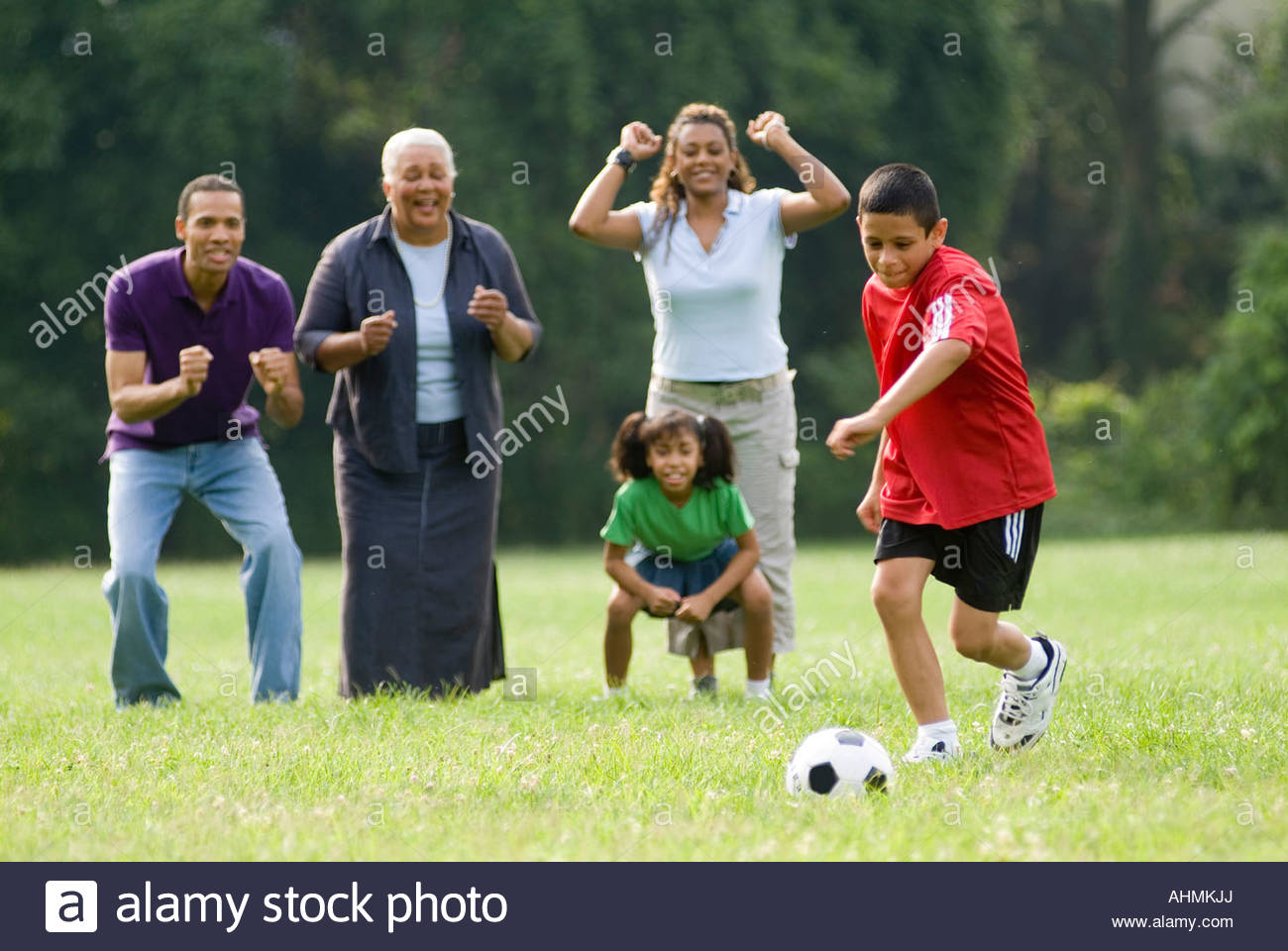 Young boy kicking soccer ball as family watches - Stock Image