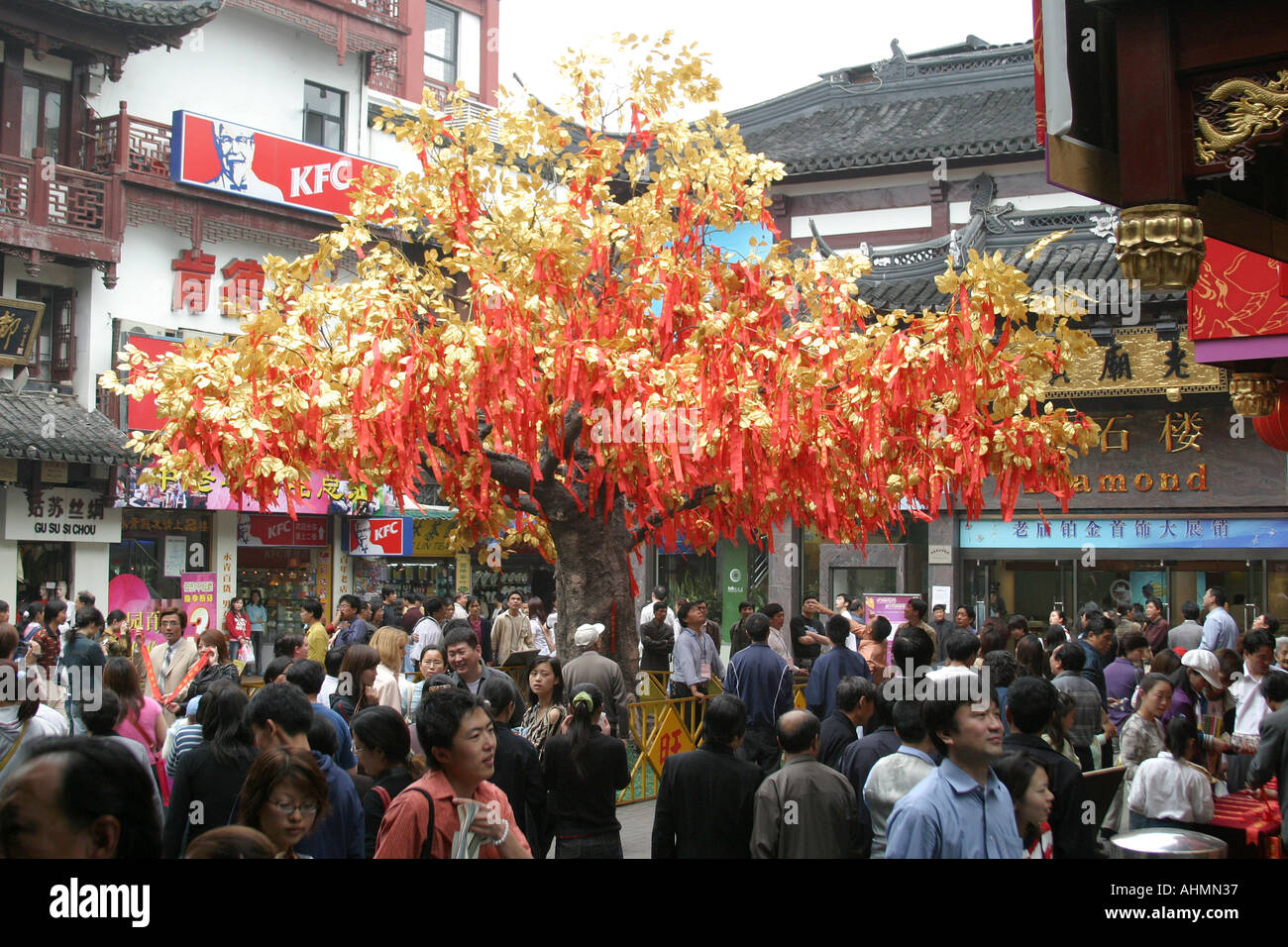 crowd around a gold leaf wish tree in shanghai stock image