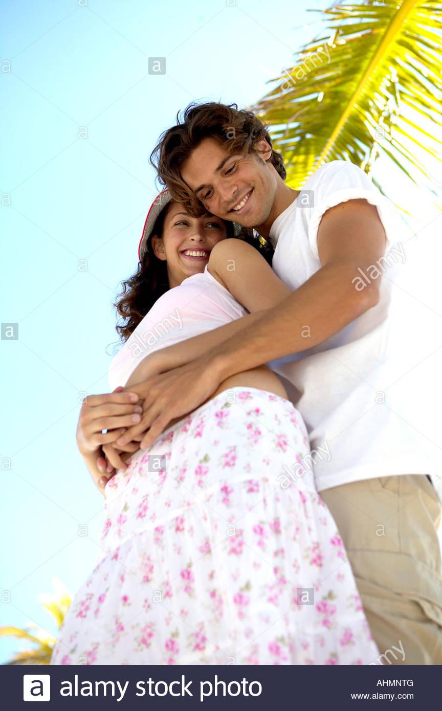 Young Hispanic couple hugging - Stock Image