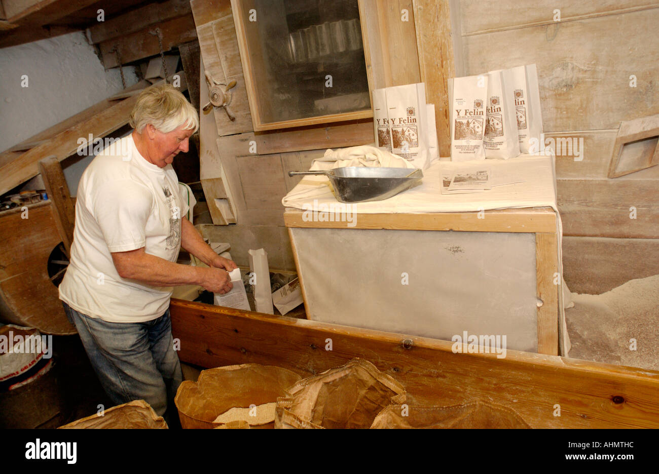 Miller working in small bag weighing area in 17th century Y Felin flour mill at St Dogmaels Pembrokeshire West Wales UK - Stock Image