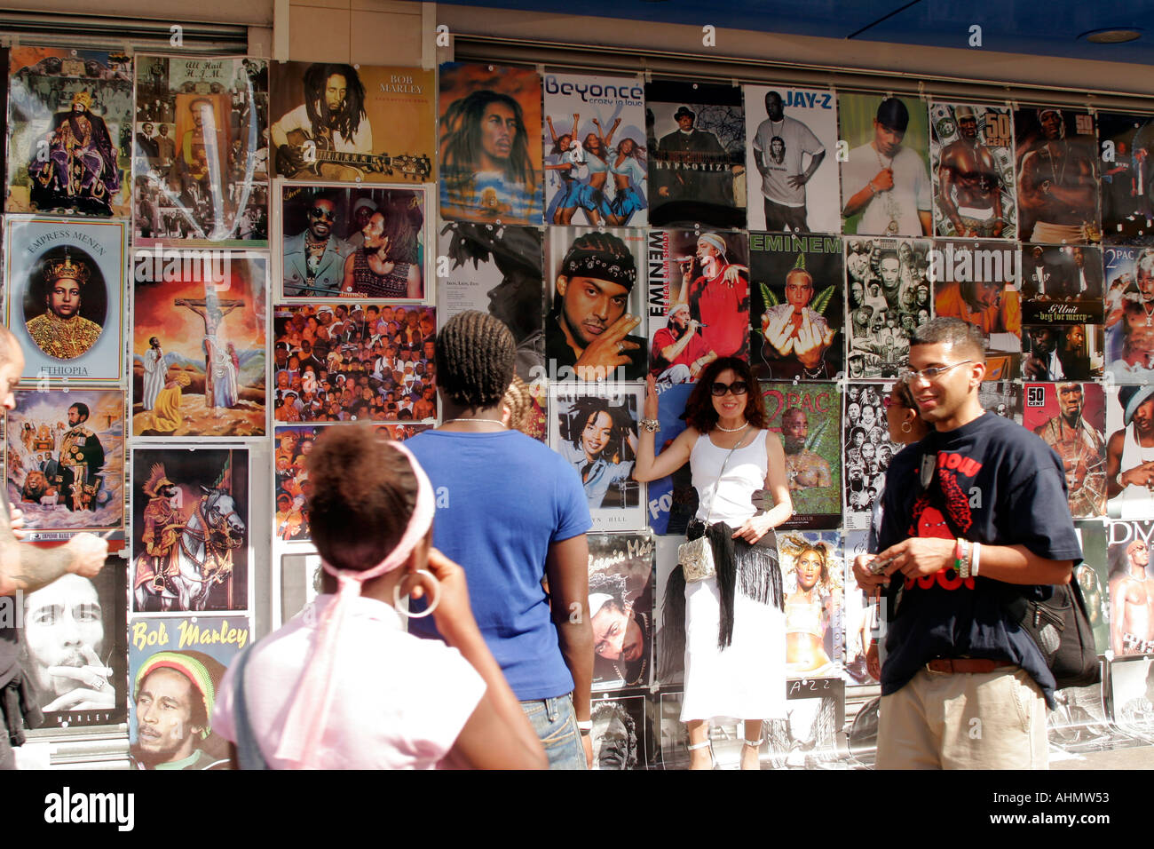 united kingdom london notting hill woman posing with passers by in front of billboards - Stock Image