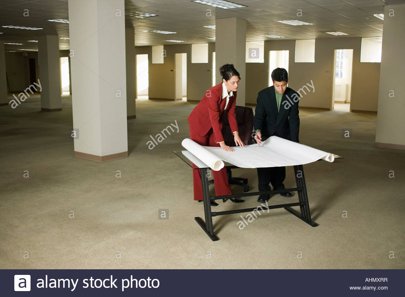 Businesspeople looking at blueprints - Stock Image