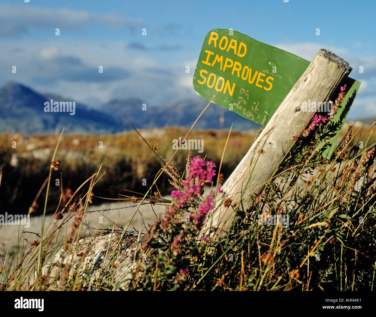Country road County Galway Republic of Ireland Hand written sign saying Road Improves Soon and Oh No It Doesn t - Stock Image