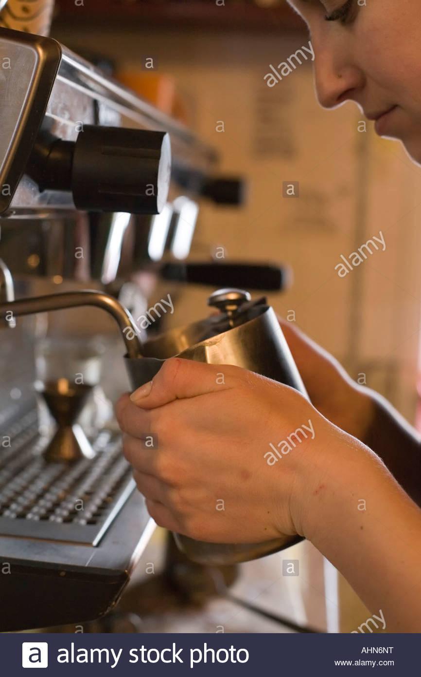 Woman filling metal pitcher - Stock Image