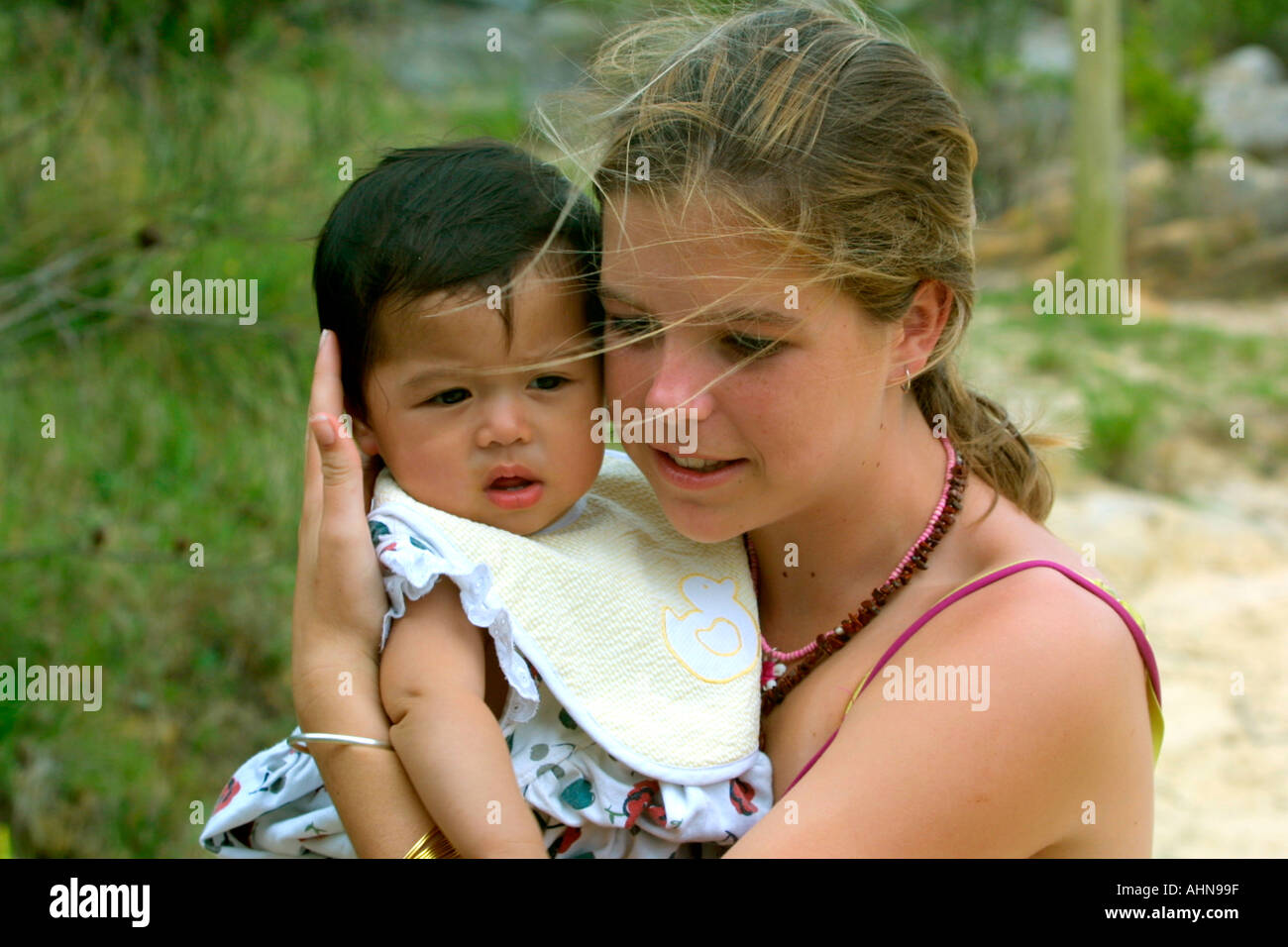 Teen girl holds a baby - Stock Image