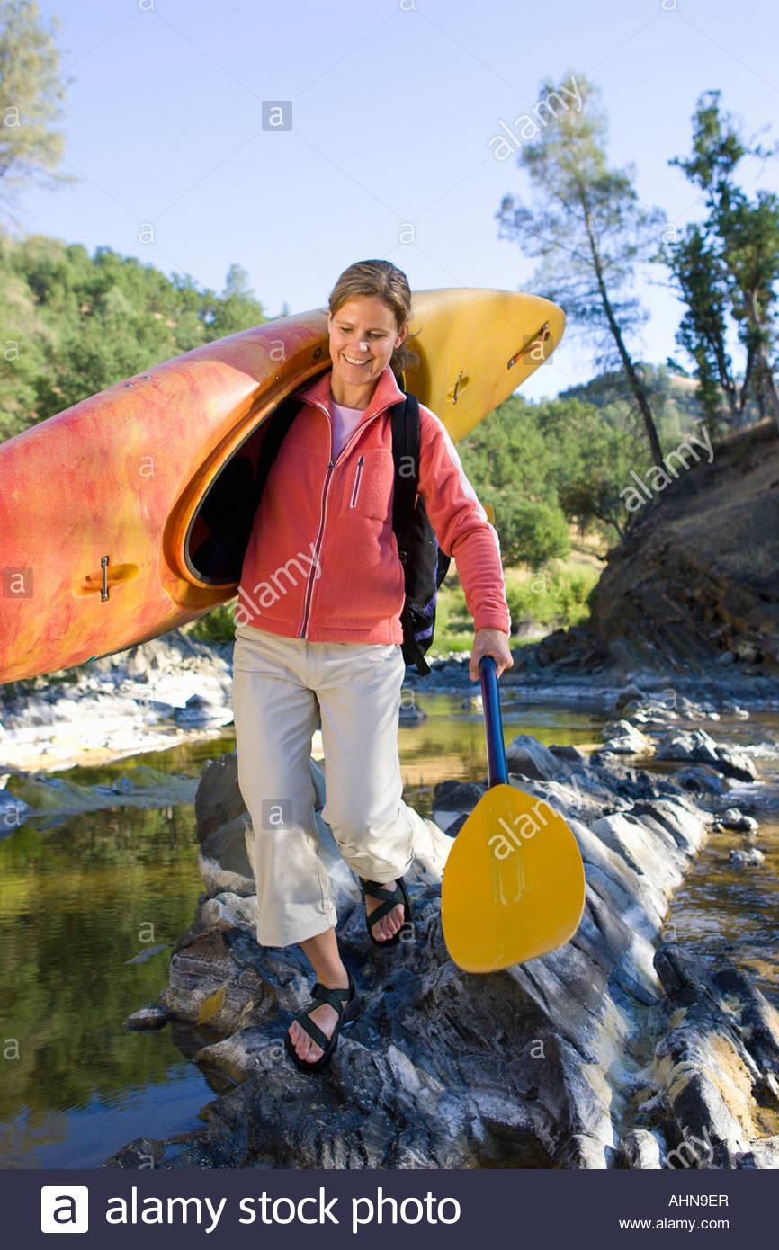 Woman carrying kayak across craggy stream - Stock Image