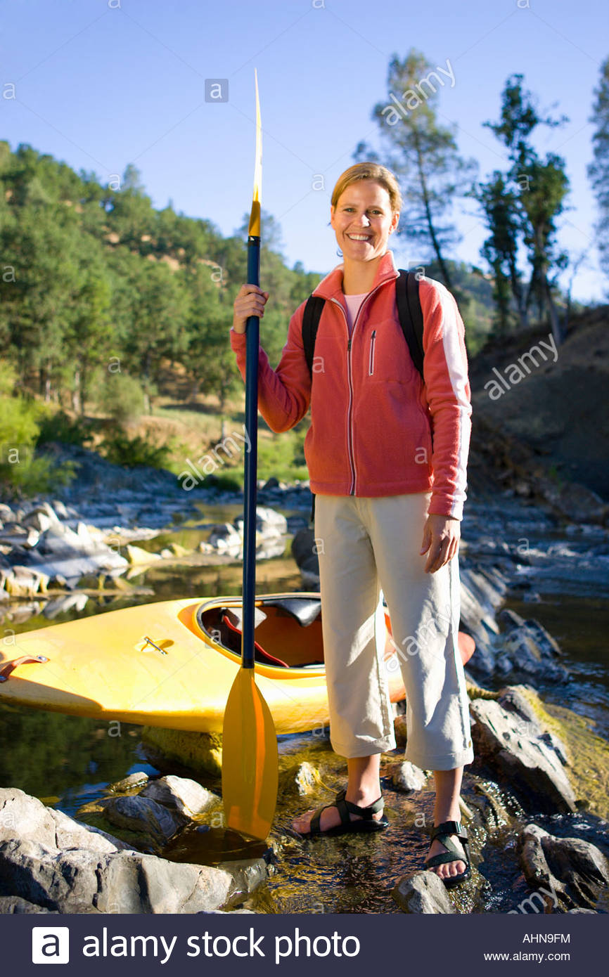Woman with oar and kayak by craggy stream - Stock Image