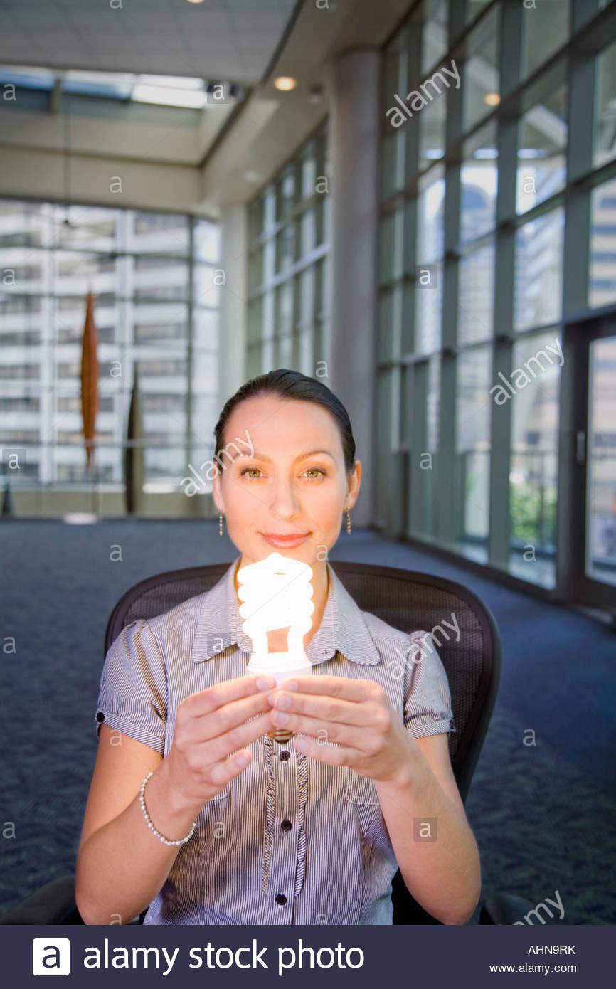 Businesswoman holding energy efficient light bulb - Stock Image