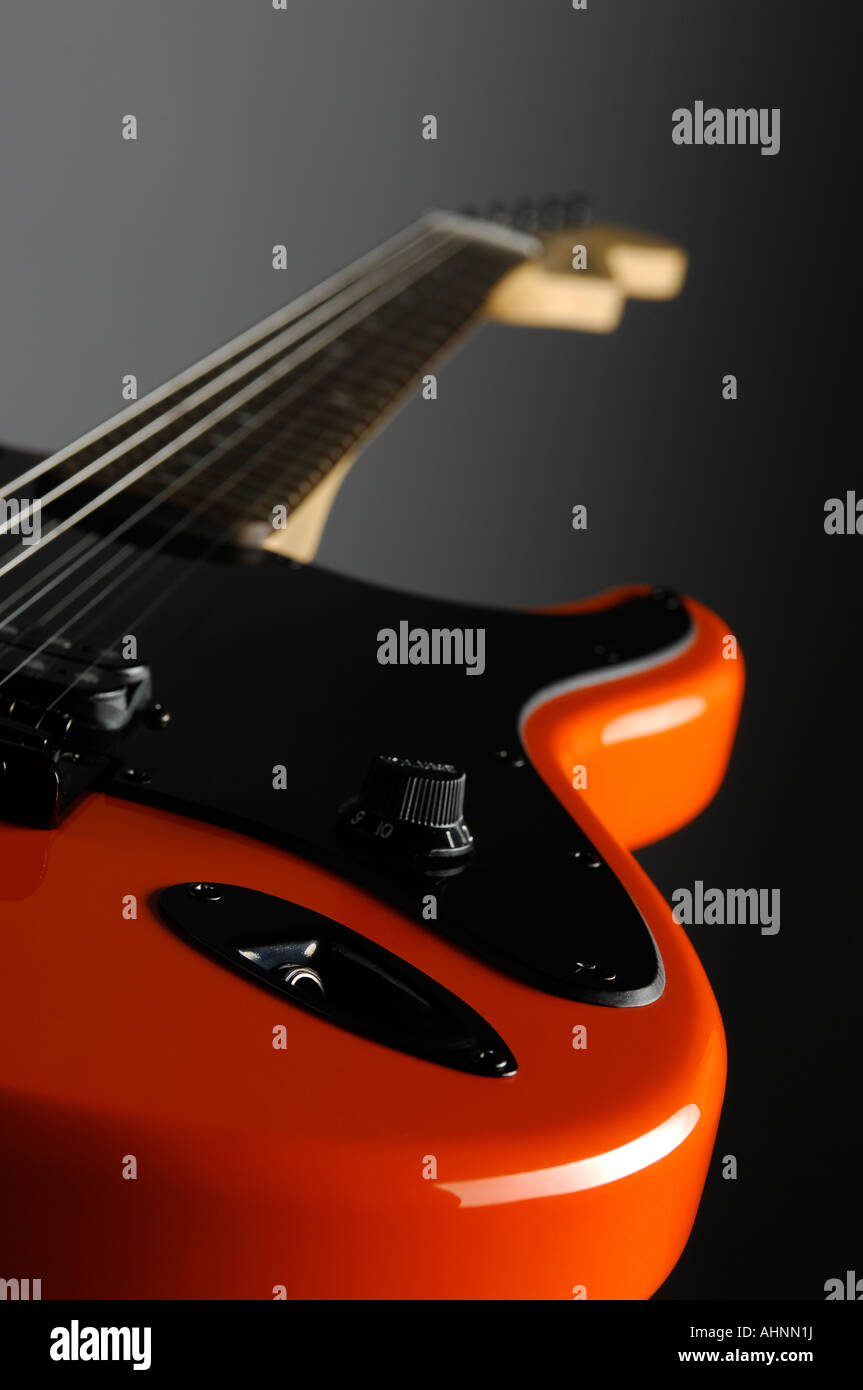 wide angle view of orange electric guitar looking from jack socket to neck Stock Photo