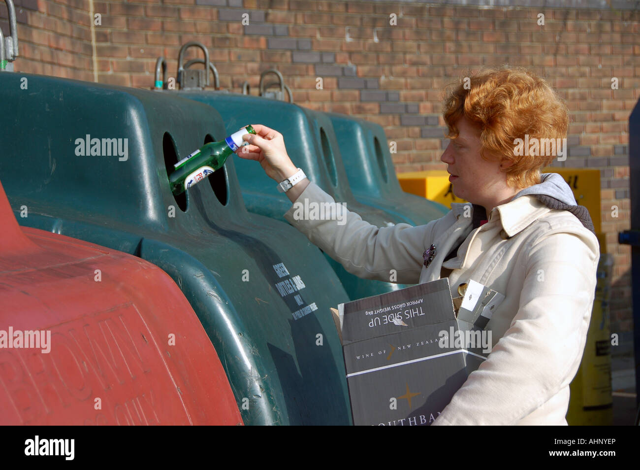 A woman recycling bottles at a bottle bank - Stock Image