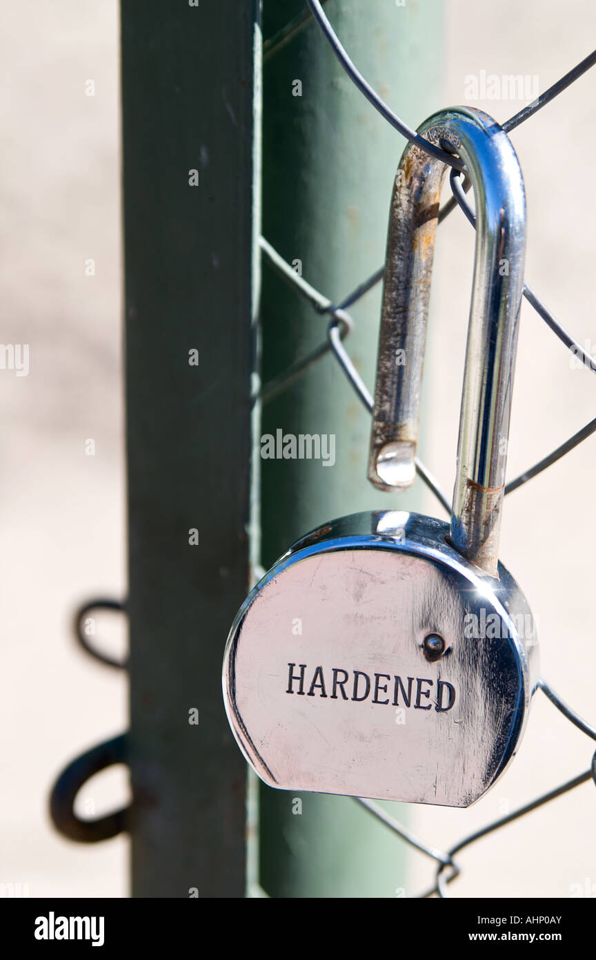 Broken chrome plated hardened padlock beside open gate - Stock Image