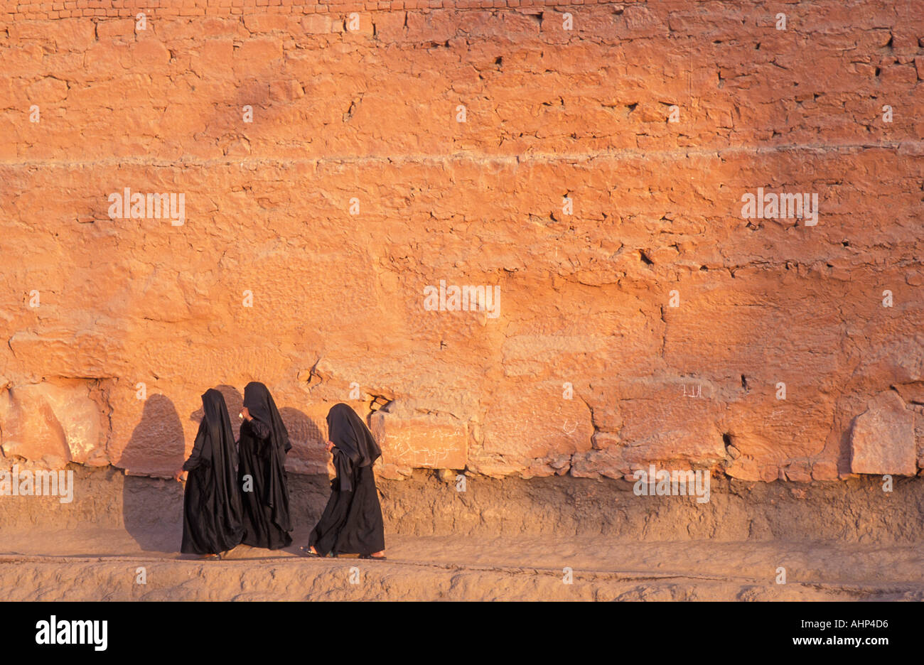 Muslim women robed in black burqas walking along the outer wall path of Karnak Temple Nr Luxor Egypt Photo by Jamie Marshall - Stock Image