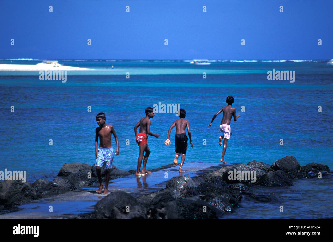 Kids running and jumping off a jetty into the sea off the coast of Mauritius Indian Ocean - Stock Image