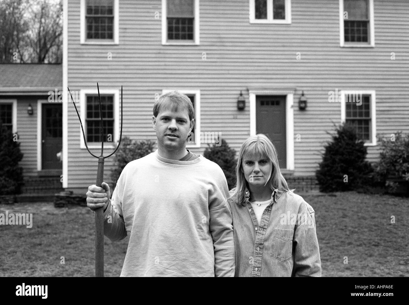 Two people homeowners standing in front of home with pitchfork American Gothic homage Modern version of painting by Grant Wood - Stock Image