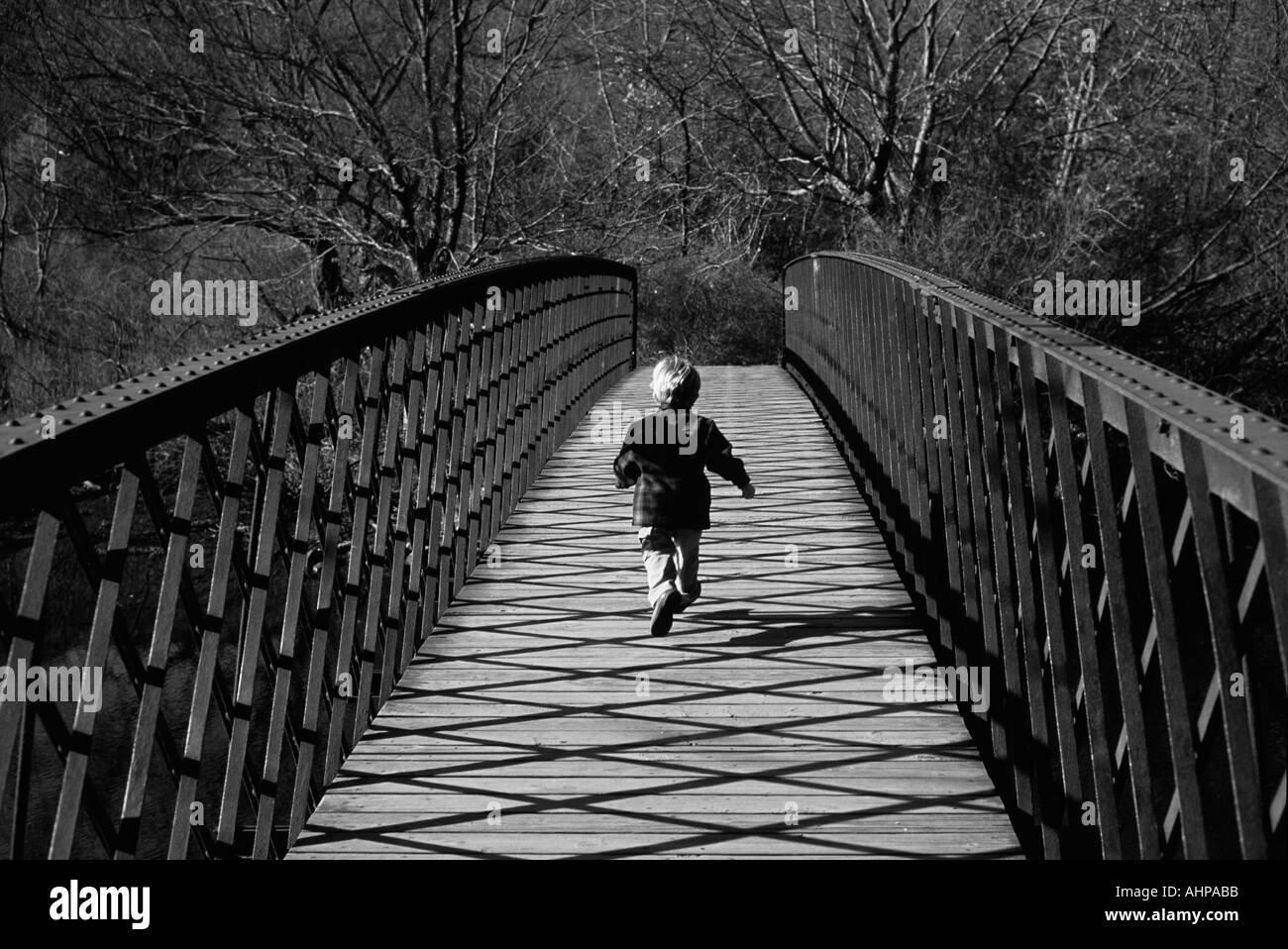 Boy running across bridge black and white - Stock Image