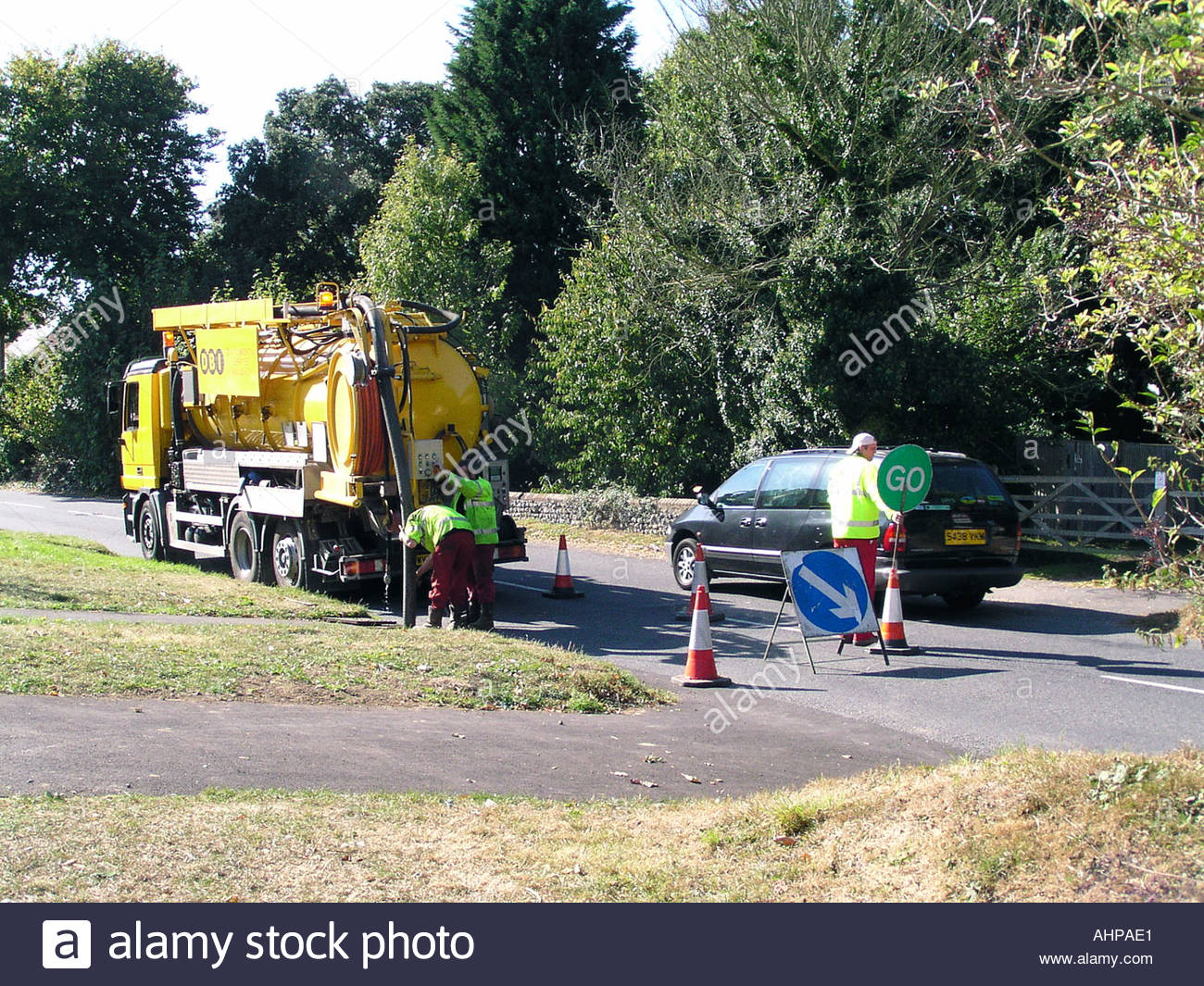 Environmental services workmen cleaning drains in country lane Ferring Sussex with one lane of road closed to cars UK - Stock Image
