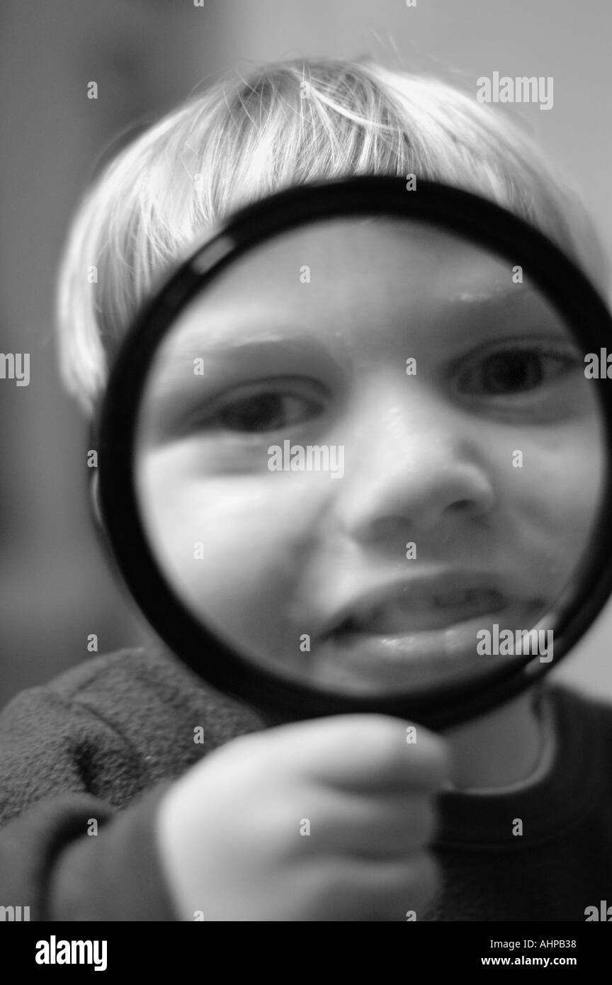 Child exploring using holding magnifying glass - Stock Image