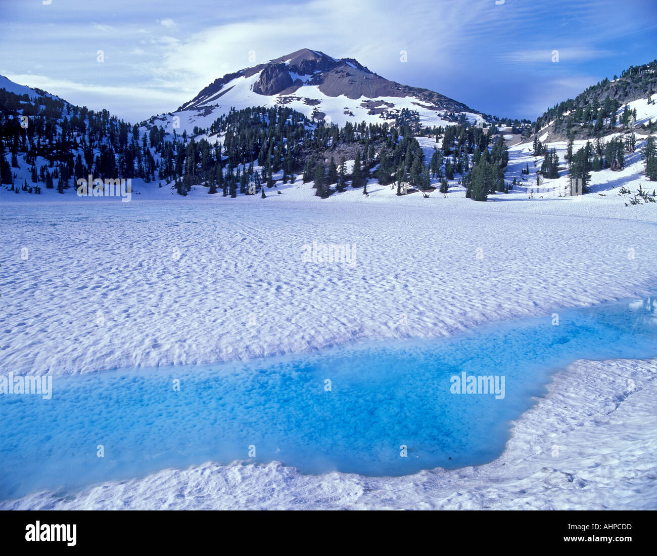 Azure water on shore of thawing Lake Helen with Mount Lassen California - Stock Image