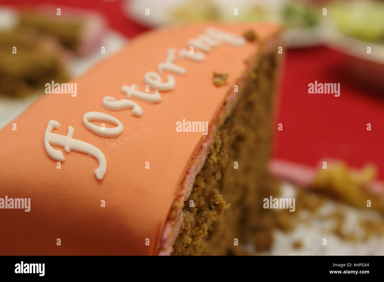 A slice of cake with the word Fostering iced on it. - Stock Image