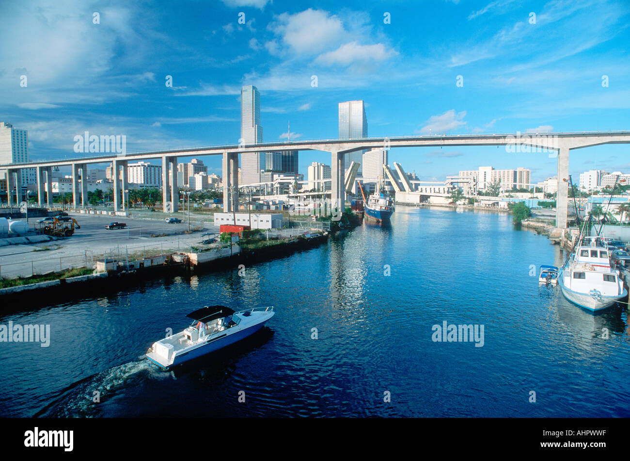 Waterway underneath metro rail line with skyline in background in Miami Florida - Stock Image