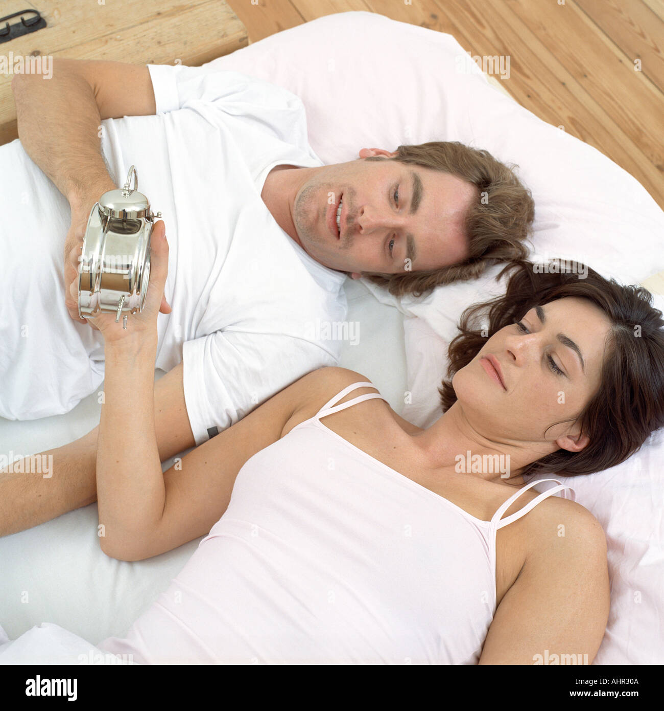 couple in bed looking at clock stock photo 2700041 alamy