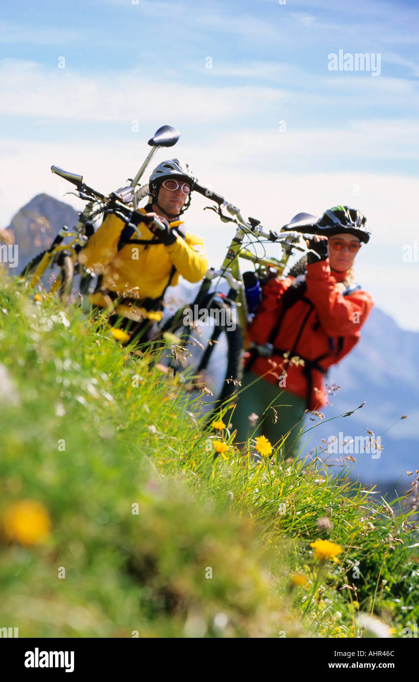 Mountain bikers carrying their bicycles - Stock Image