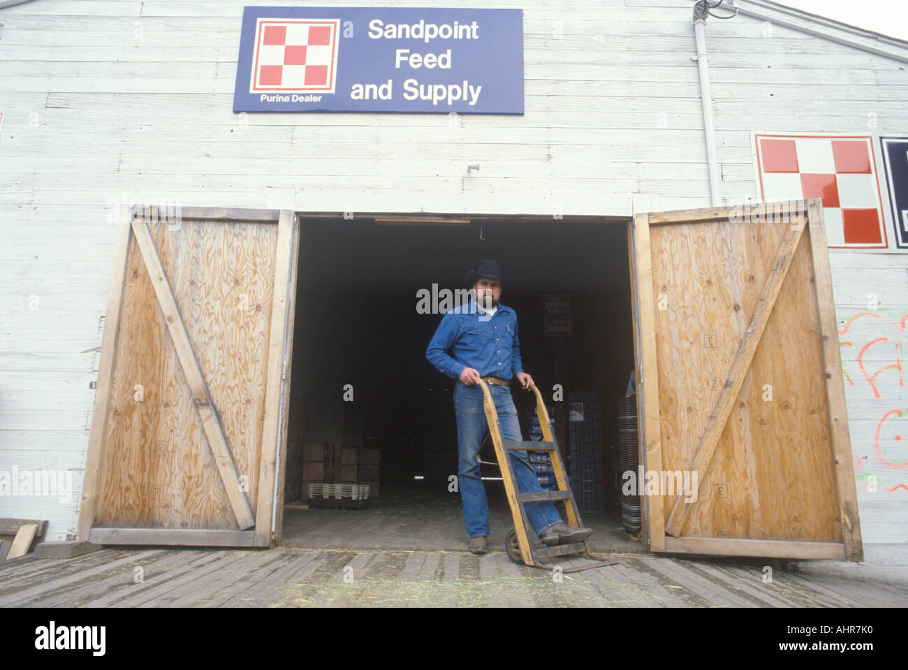 Man coming out of a feed store in Sandpoint ID - Stock Image