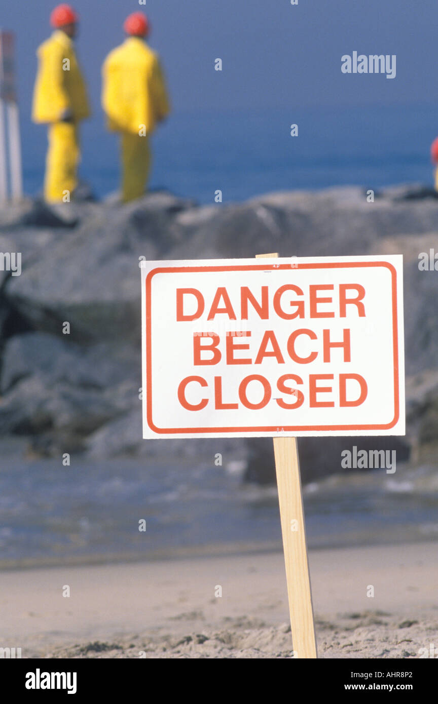 A sign warning danger beach closed with cleanup crews in the background - Stock Image