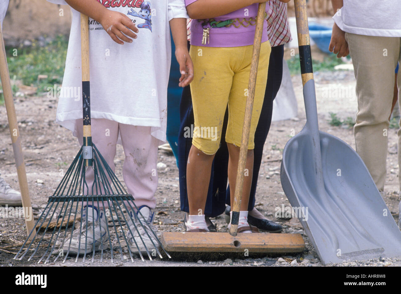 A close up of women holding cleanup tools - Stock Image