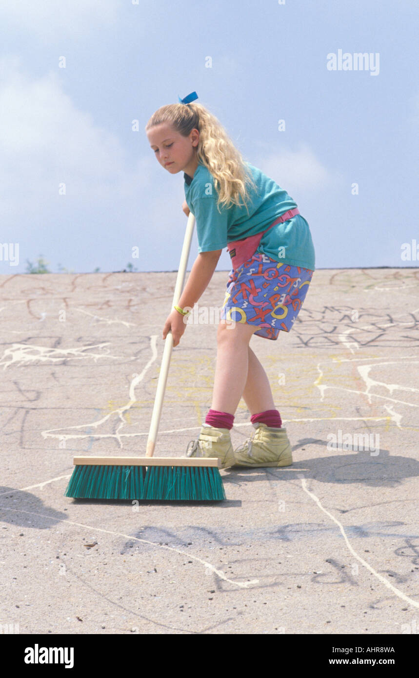 A young girl cleaning up with a push broom - Stock Image