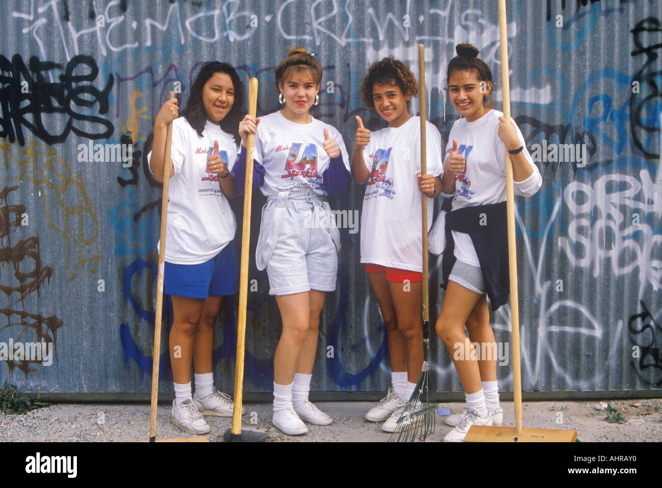 Four teenage girls participating in community cleanup on Clean and Green Day in East Los Angeles California - Stock Image