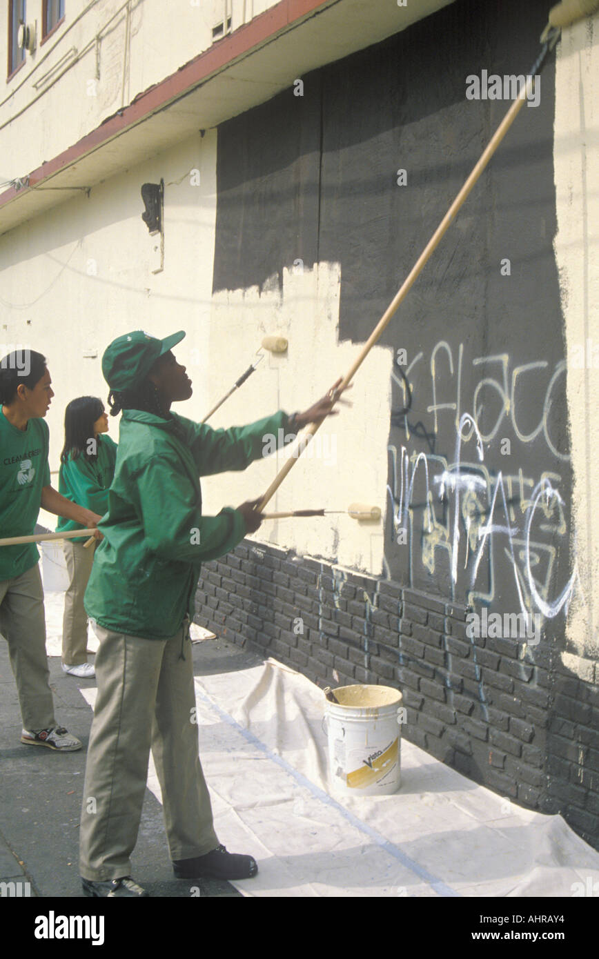 A group of kids repainting the side of a building defaced by graffiti - Stock Image