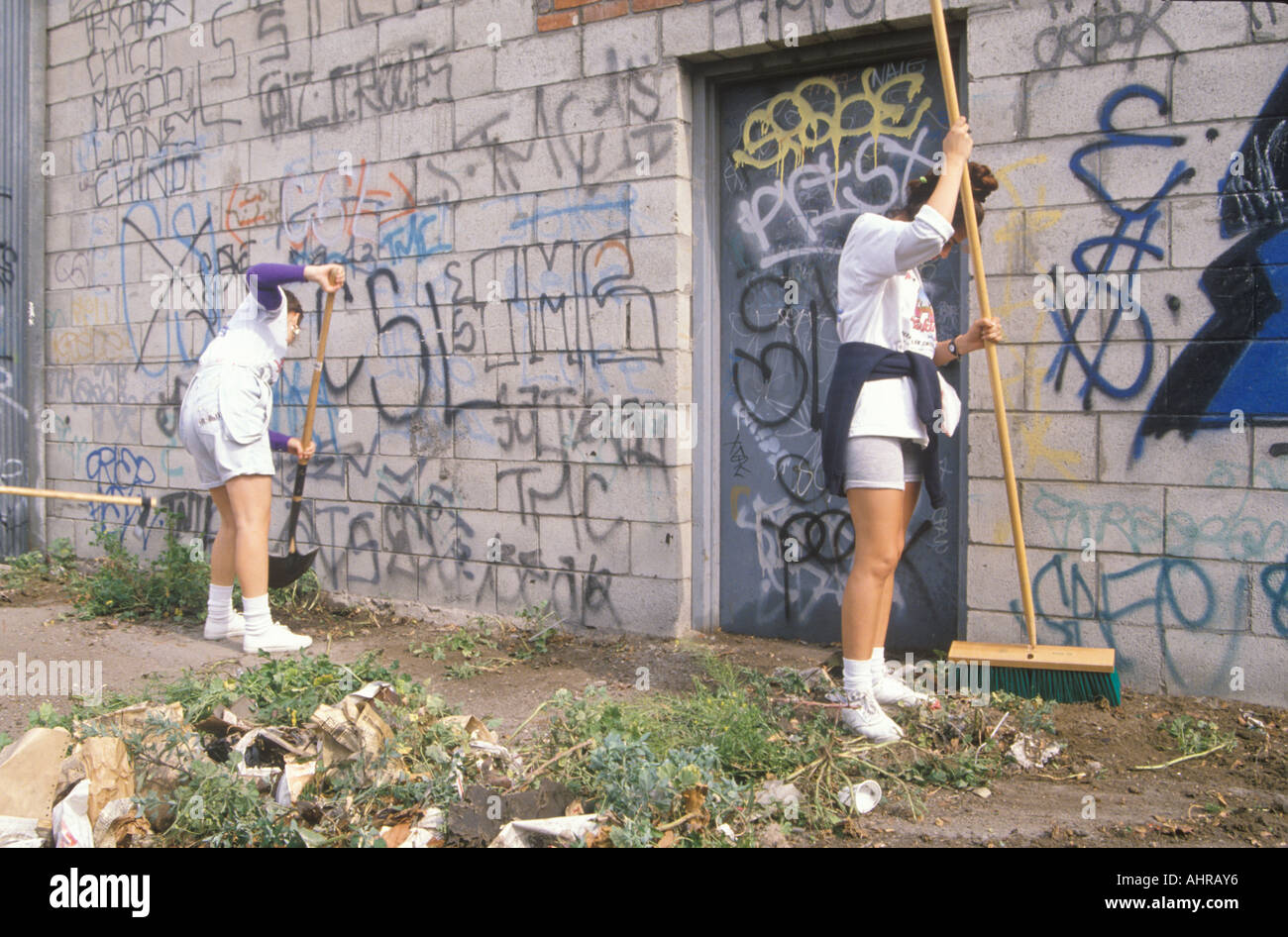 A group of young people participating in community cleanup by sweeping an alley - Stock Image