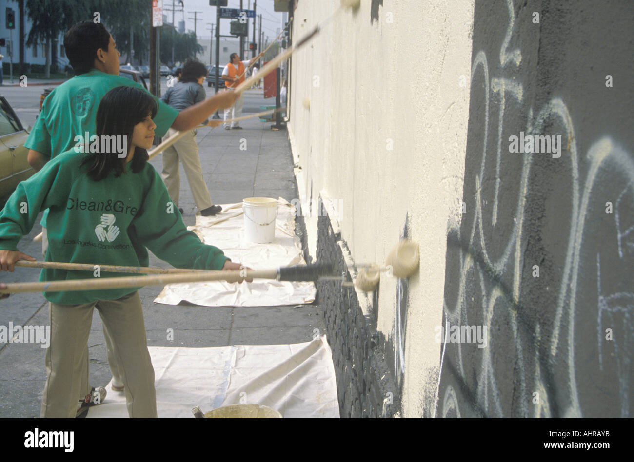 Several community members participate in covering graffiti for Clean Green Day an urban cleanup pro B302ject in East Los - Stock Image