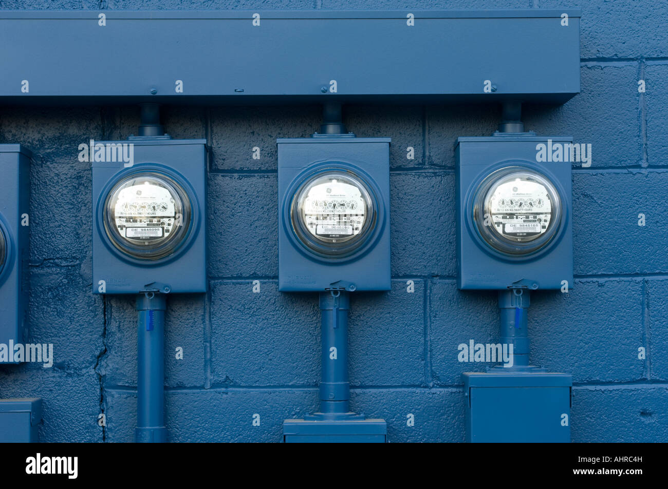 Three electric power meters and blue wall - Stock Image