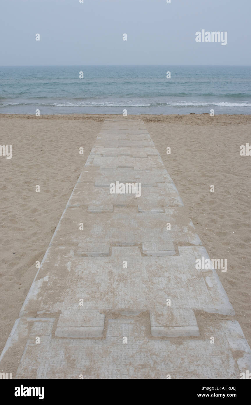 Concrete path leading to the Mediterranee sea across a sandy beach - Stock Image