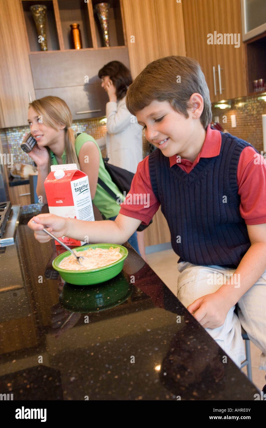 Boy stirring cereal, girl and Mom on phone - Stock Image