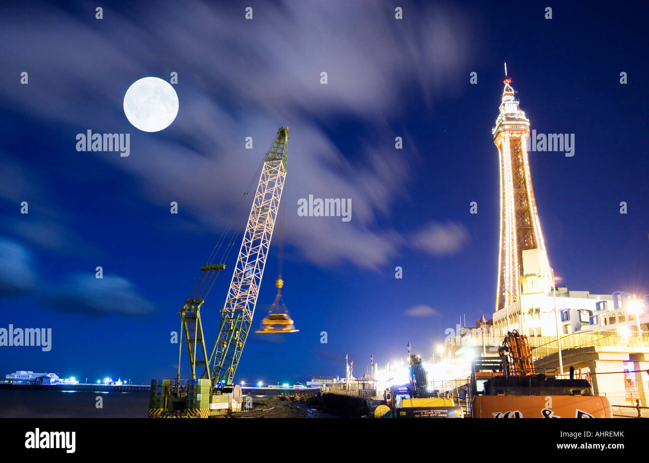 Blackpool tower and crane by moonlight during the building of the new sea defences Stock Photo