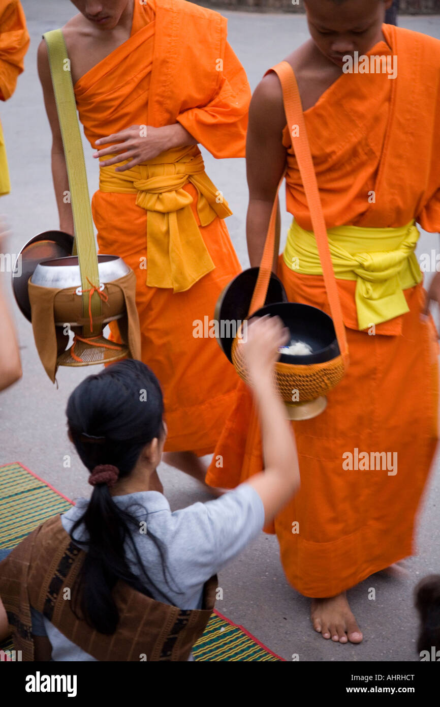 Local women give rice Alms to monks in Luang Prabang Laos Stock Photo