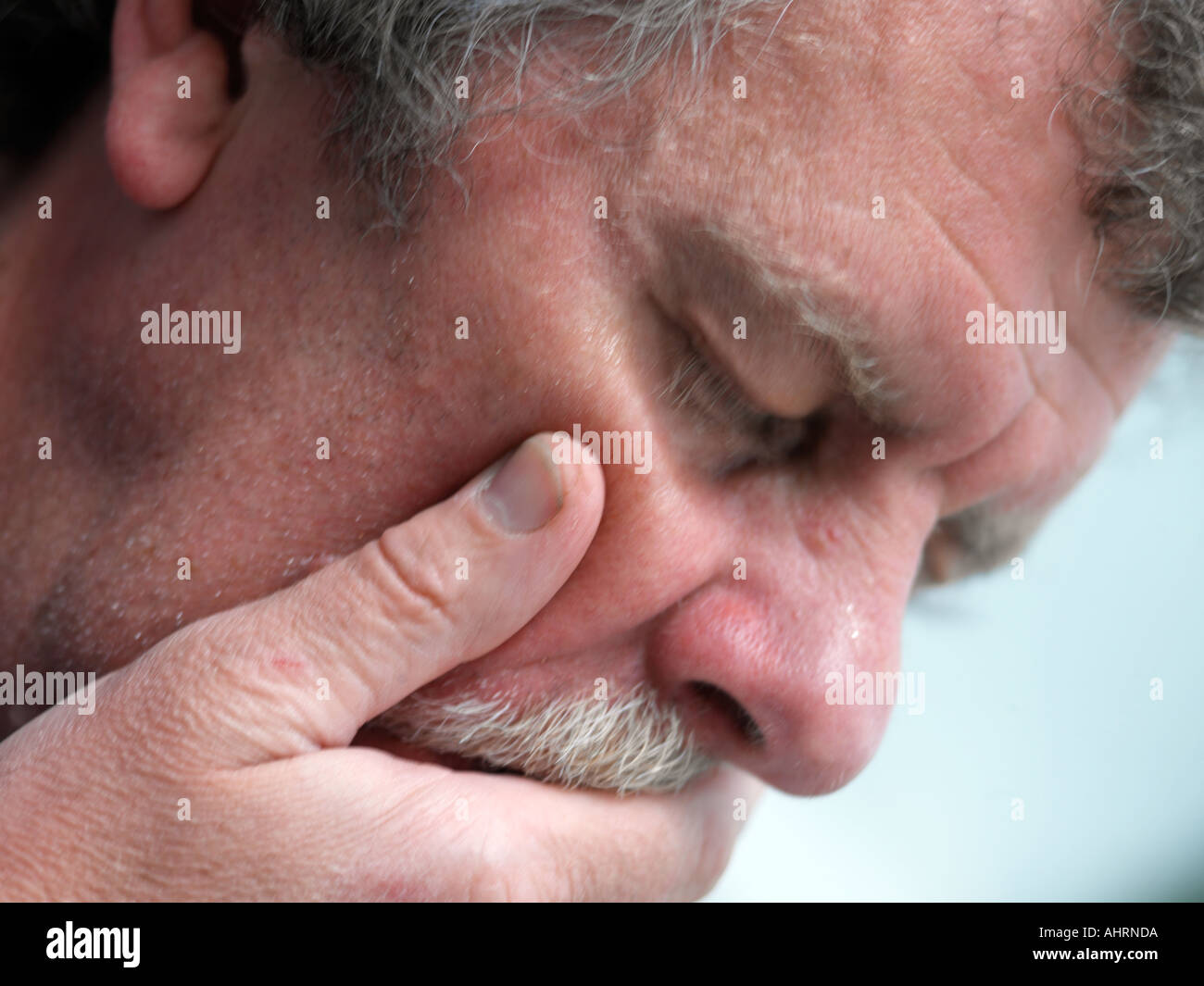 Man Choking Hand Across Face - Stock Image