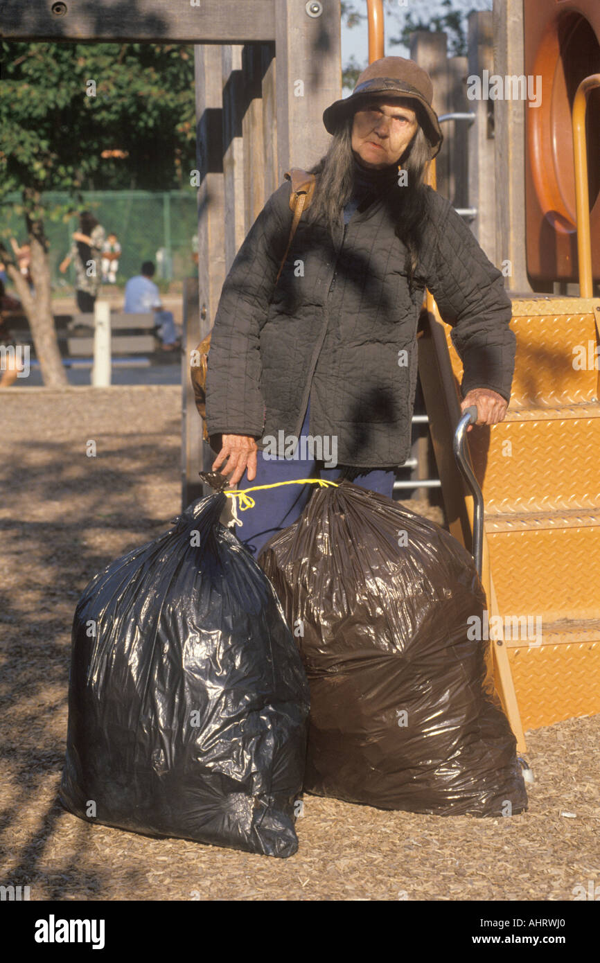 Elderly homeless woman holding possessions in garbage bags Chicago Illinois - Stock Image