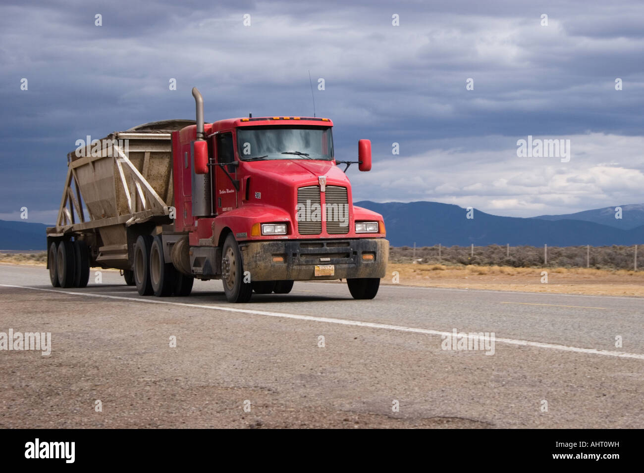 Cargo truck travelling along the highway under a cloudy sky. Stock Photo