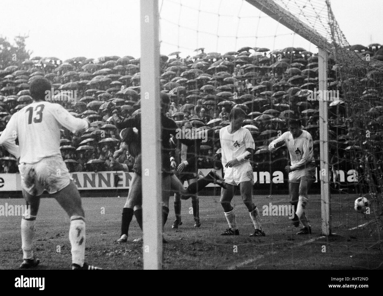 football, Bundesliga, 1970/1971, Boekelberg Stadium, Borussia Moenchengladbach versus 1. FC Cologne 1:1, game took place in constant rain, visitors and football fans with umbrellas, scene of the match, f.l.t.r. Thomas Parits (Koeln), keeper Manfred Mangli - Stock Image
