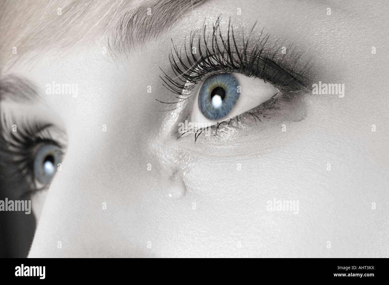Blue tearful female eye with makeup running - Stock Image