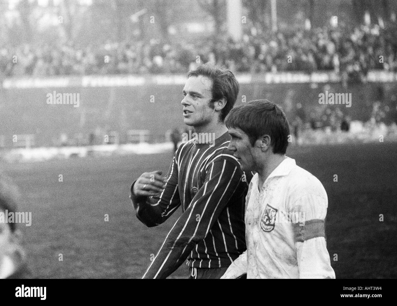 football, Regionalliga West, 1970/1971, Stadium am Zoo in Wuppertal, Wuppertaler SV versus Fortuna Duesseldorf 1:1, football players leaving the pitch, left Klaus Budde (Ddorf), right Manfred Reichert (WSV) - Stock Image
